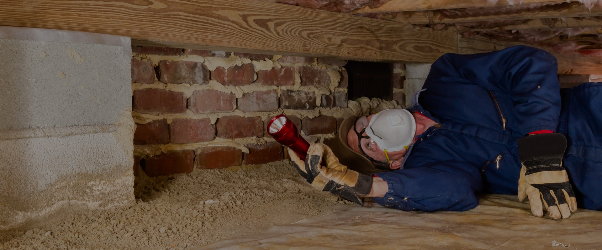 man inspecting crawl space